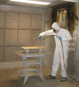 Craig in a dry suit spraying a wood panel